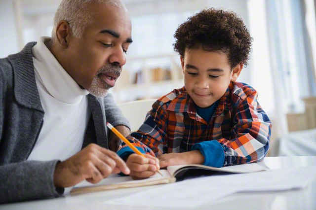 Mixed race grandfather helping grandson do homework
